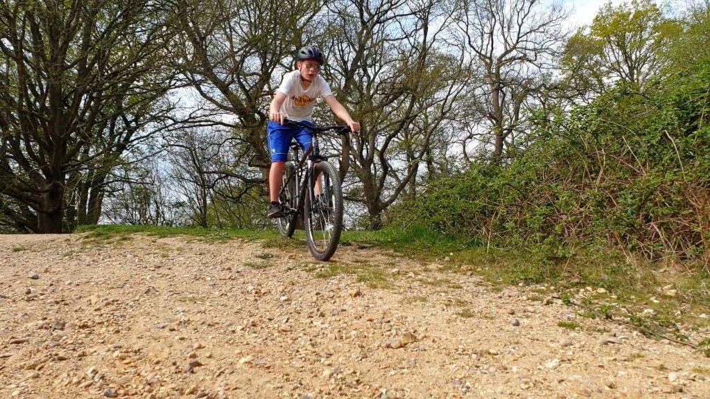 A photo of a boy riding a mountain bike down a gravel path